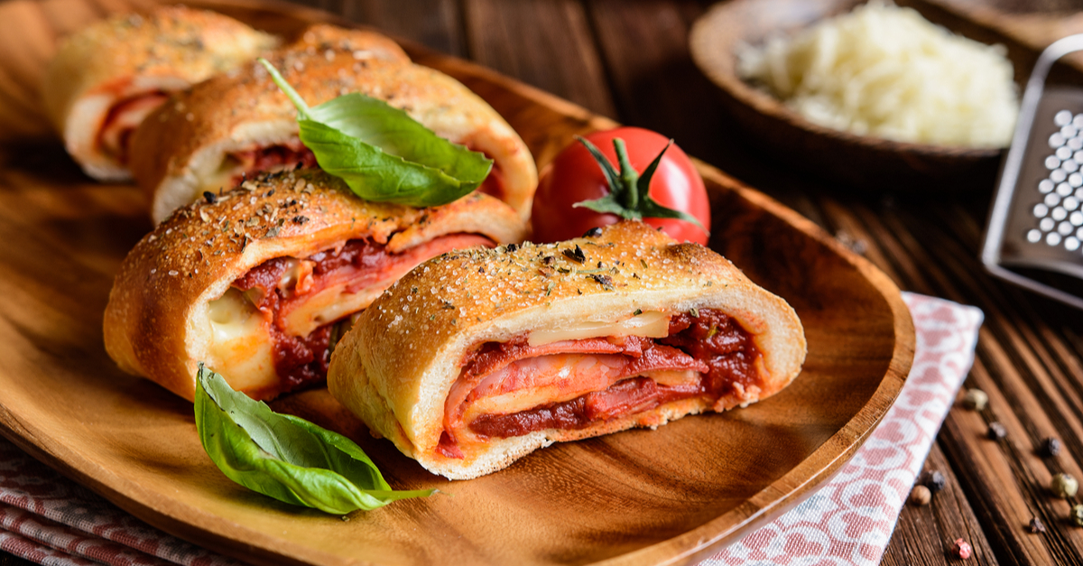 Фото Стромболи - это невероятно вкусная и ароматная пицца-рулет, имеющая итальянское или итало-американское происхождение. По своему приготовлению она напоминает обычную пиццу, однако, пласт теста вместе с ингредиентами скатывается в рулет. Попробуйте и