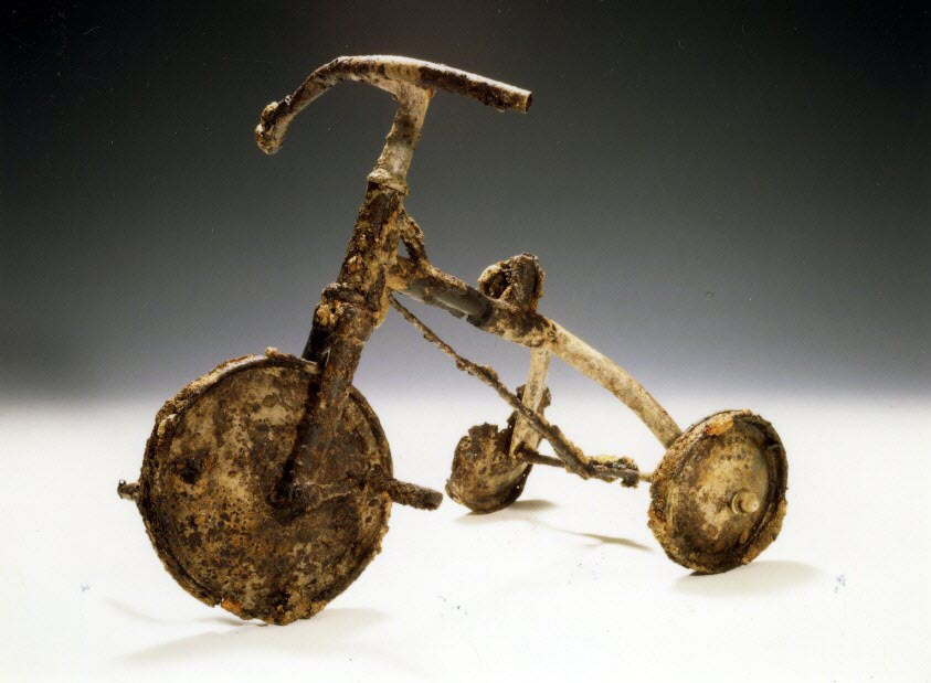 Photo of Behind a glass case at the Hiroshima Peace Memorial Museum is a battered and rusted tricycle. The seat is missing, and so are the pedals and the handle grips, and the entire metal frame of the cycle
