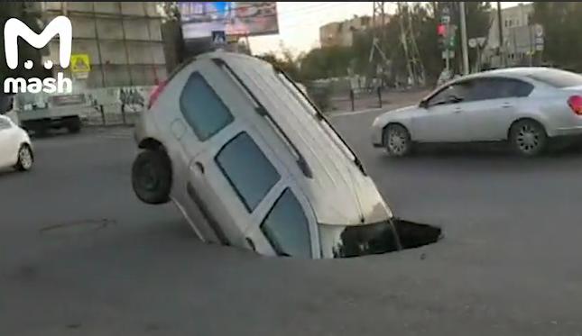 Провал на дороге наполовину поглотил автомобиль в Астрахани