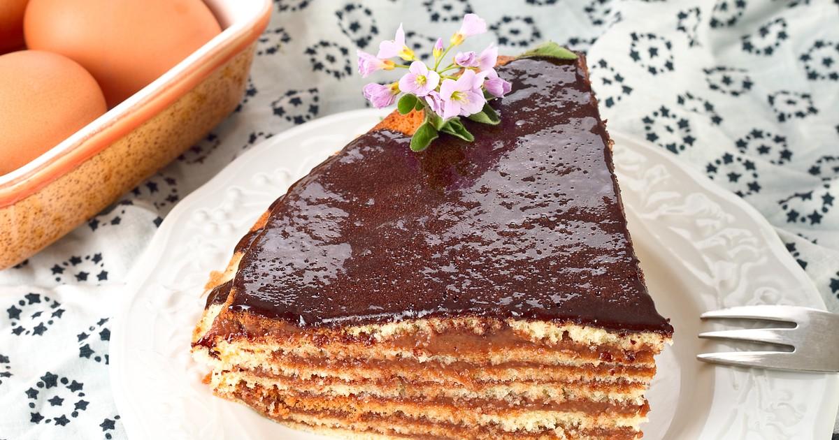 Фото Роскошный многослойный торт с шоколадным кремом, залитый шоколадной глазурью.