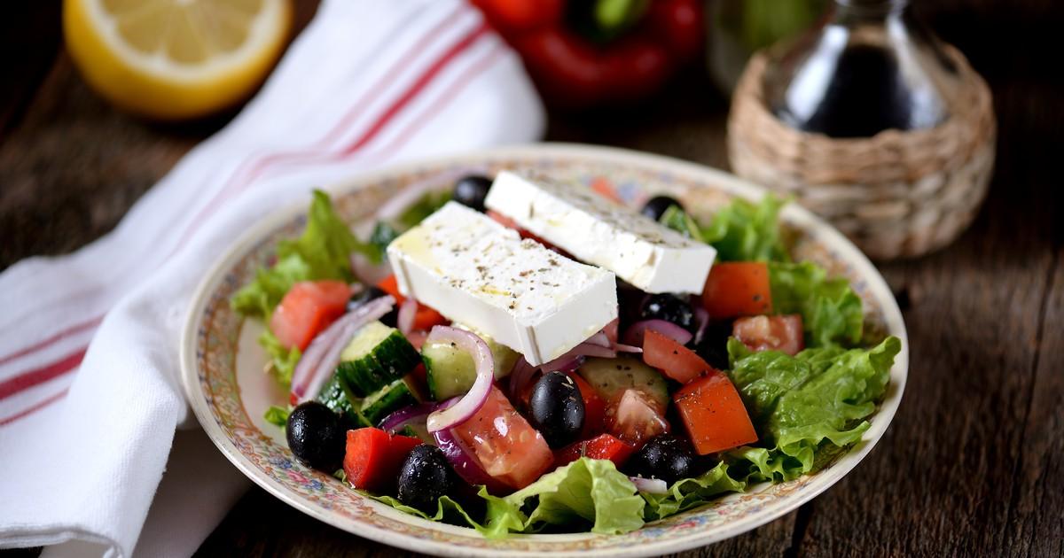 Фото Греческий салат – идеальный вариант замечательного блюда с ресторанным видом и вкусом. Традиционно овощи в этом салате не смешивают с сыром. Сыр нарезают крупными толстыми ломтиками и выкладывают поверх всех овощей. Рецепт греческого салата недорог