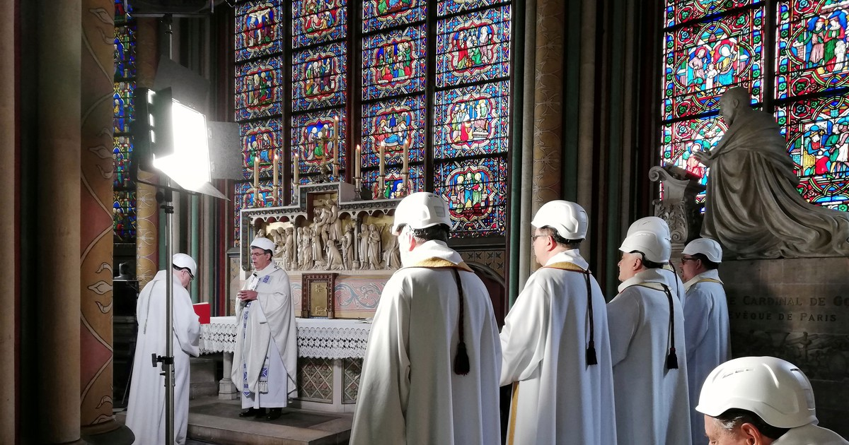 Photo of Priests in hard hats celebrate the first mass at Notre Dame since the devastating fire