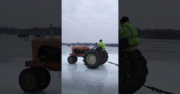 Dude chills on a couch while a tractor pulls him across a frozen lake