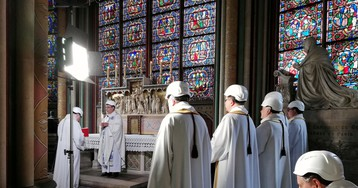 Priests in hard hats celebrate the first mass at Notre Dame since the devastating fire