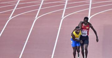 Jonathan Busby, de Aruba, completa los 5.000 metros ayudado por otro atleta