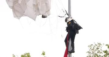 Un paracaidista choca y se queda enganchado en una farola en el desfile del 12 de Octubre
