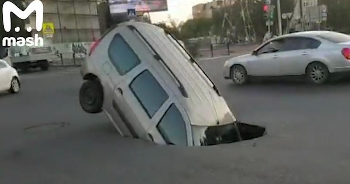 Фото Провал на дороге наполовину поглотил автомобиль в Астрахани